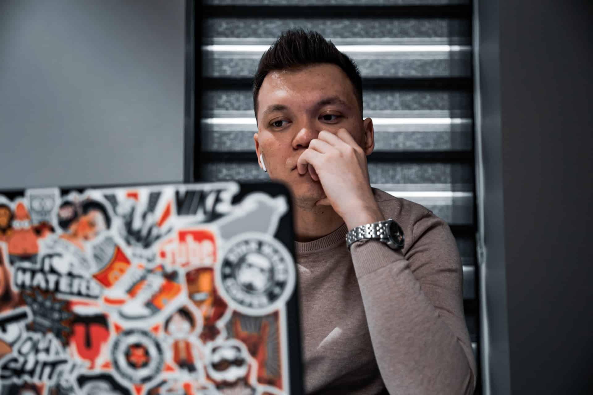 Man using laptop and thinking