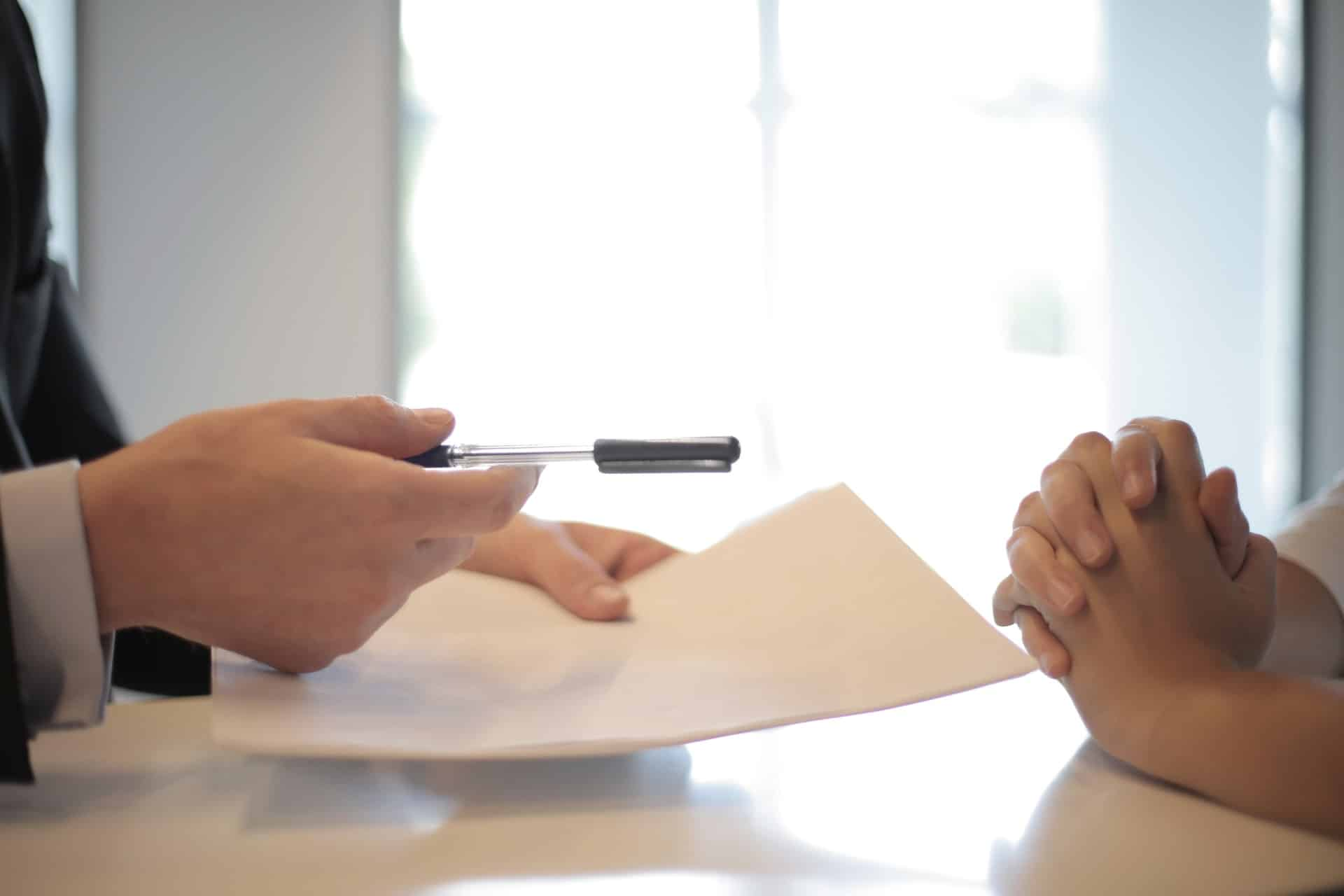 Person handing pen and paper