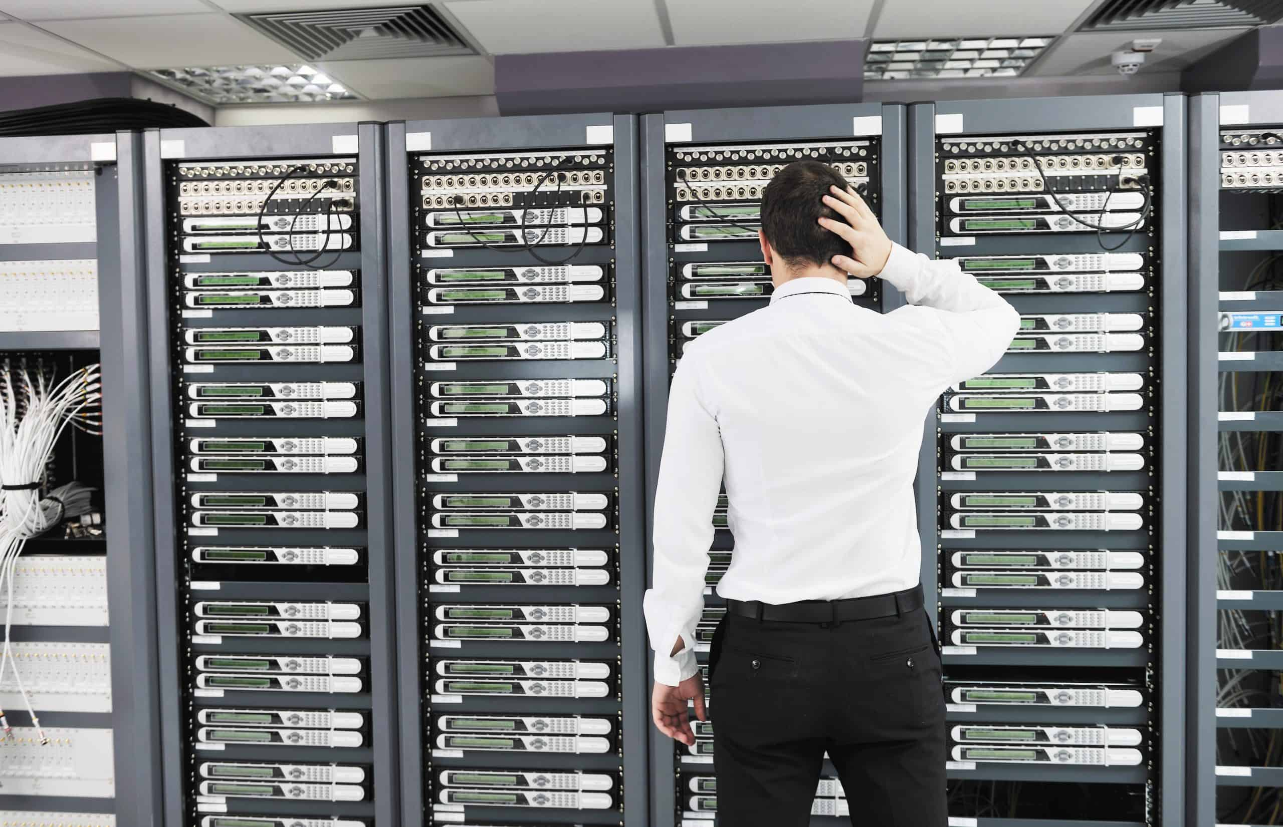 Man holding head in front of server